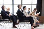 Multikulturelle Geschäftsleute in medizinischen Masken sitzen während des Seminars im Konferenzraum