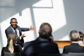 usmívající se africký americký přednášející ukazuje rukama v blízkosti obchodníků na rozmazané popředí