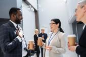 usmívající se multietnické obchodní kolegové s kávou jít mluvit během setkání