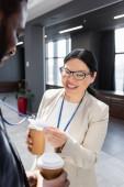 fröhliche asiatische Geschäftsfrau schaut auf Ausweis eines afrikanisch-amerikanischen Kollegen