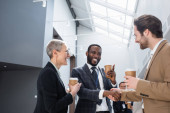 šťastný africký americký podnikatel potřást rukou s mladým kolegou během přestávky na kávu