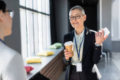 smiling businesswoman with smartphone and paper cup talking to blurred colleague