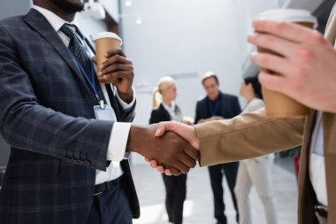 Interracial businessmen shaking hands near colleagues on blurred background stock vector