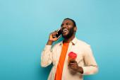 nevetés afro-amerikai férfi elvitelre ital beszél okostelefon kék háttér