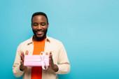 elégedett afro-amerikai férfi kezében ajándékdoboz elszigetelt kék