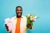 boldog afro-amerikai férfi ajándékdobozzal és tulipánokkal nevetnek a kék kamerán