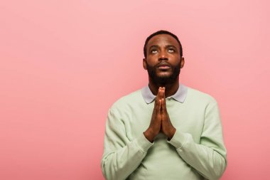 African american man with praying hands looking up isolated on pink stock vector