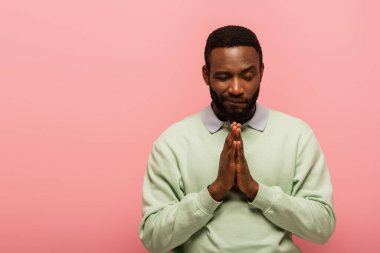 African american man standing with praying hands isolated on pink stock vector