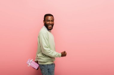 Excited african american man with gift box behind back showing yeah gesture on pink background stock vector