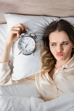 Top view of sad woman holding alarm clock on bed stock vector