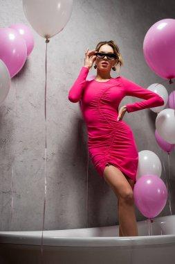 Pembe elbiseli ve güneş gözlüklü şık bir kadın parti sırasında balonların yanında duruyor.