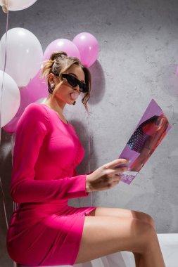 Banyoda balonların yanında sakız okuyan modaya uygun bir kadın.