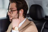 szakállas férfi szemüvegben és bézs kabát állító vezeték nélküli fülhallgató autóban