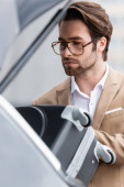 bearded man in glasses and suit putting suitcase in blurred car trunk