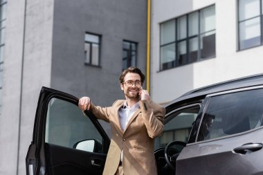 Cheerful man in suit and glasses talking on smartphone and standing near car with opened door stock vector