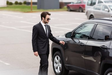 Bearded bodyguard in suit and sunglasses with security earpiece walking near modern car stock vector