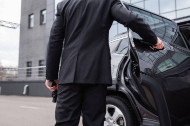Back view of bodyguard in suit holding gun and opening car door stock vector