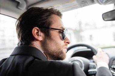 Bearded bodyguard in sunglasses driving modern automobile stock vector