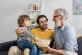 Reifer Mann hält Popcorn in der Nähe von Enkel und Sohn