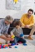 Großvater spielt mit Enkel Bauklötze neben lächelndem Sohn auf Couch