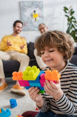 Smiling boy playing building blocks near father and grandfather on blurred background stock vector