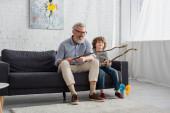 Pozitivní dědeček s hračkou rybářský prut hrát s vnukem