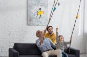 Nadšený dítě hrát hračku rybaření s otcem a dědečkem