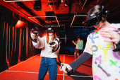 multiethnic friends in vr headsets gaming in play zone
