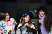 multietnikus barátok nevet közelében megdöbbent lány autóverseny szimulátor