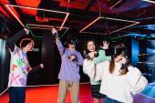 fröhlicher Teenager zeigt Siegergeste bei multikulturellen Freunden im vr Spielzimmer