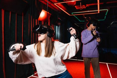 Astonished girl gaming in vr headset near blurred friend stock vector