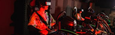 Amazed gamer racing on car simulator near blurred friends, banner stock vector