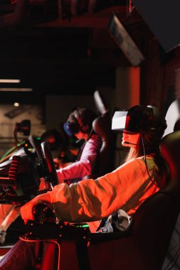 Teenage friends in vr headsets gaming on car racing simulators stock vector
