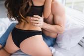 Vágott kilátás elmosódott férfi ölelés szexi nő fehérnemű