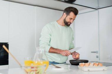 Man preparing breakfast from chicken eggs near orange juice on blurred foreground stock vector