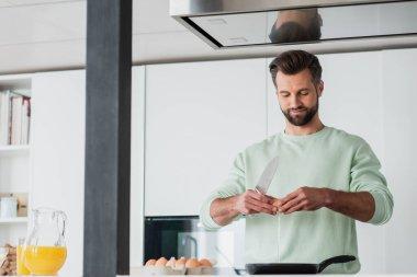 Positive man braking chicken egg near frying pen while preparing breakfast stock vector