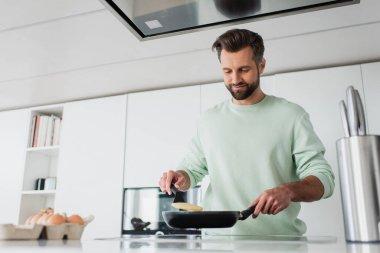 Pleased man preparing pancakes for breakfast in kitchen stock vector