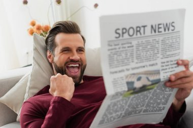 Excited man showing triumph gesture while reading sport news at home stock vector