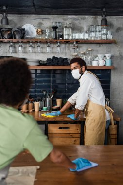 African american barista in medical mask and latex gloves cleaning worktop with rag near blurred colleague stock vector