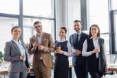 Interrassische Geschäftsleute mit Getränken und Smartphone lächeln in die Kamera