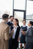 Usmívající se podnikatelka stojící poblíž kolegyně a multiethnic business lidí v úřadu