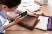 Homályos varrónő mobiltelefon tartó szövet mellett olló az asztalon