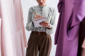 Vágott kilátás varrónő írás notebook közelében ruhák elmosódott előtérben