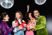 pozitivní multiraciální přátelé v barevných šatech s plastovými poháry v rukou tanec na černém pozadí