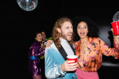 smiling multiracial couples in colorful clothes dancing in night club on black background