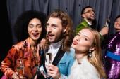 interrassische Freunde in stilvoller Kleidung grimmig und Champagner trinkend in der Nähe des grauen Vorhangs auf schwarzem Hintergrund