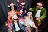 mosolygós fajok közötti barátok télapó kalap és napszemüveg ünneplő újév közelében szürke függöny fekete háttér