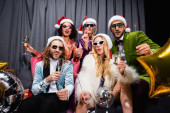 Freunde in Weihnachtsmützen feiern Neujahr in der Nähe des grauen Vorhangs auf schwarzem Hintergrund