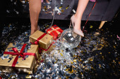 partial view of female legs in beige shoes with disco ball and gift boxes in night club