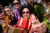 Afričanky americká žena v slunečních brýlích drží dárkové krabice mezi různými přáteli v blízkosti šedé opony na černém pozadí